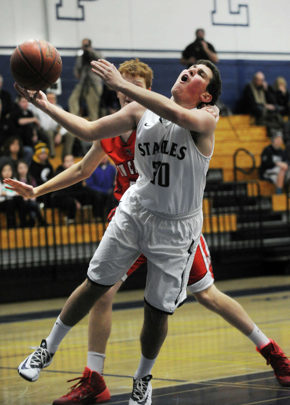 Staples' Andrew Felman is fouled by New Canaan's Andrew Penchuck as he drives to the basket during their boys basketball matchup at Staples High School in Westport, Conn. on Monday, December 30, 2013.