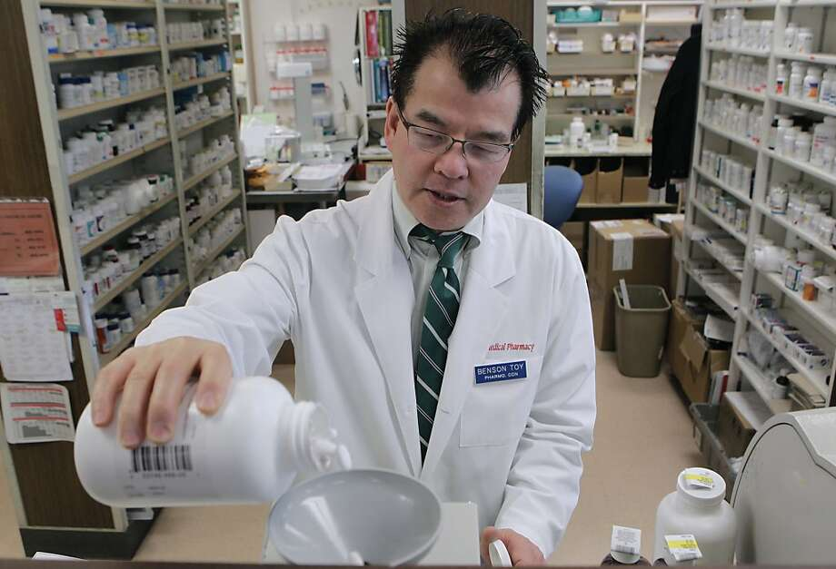 Pharmacist Benson Toy shakes ibuprofen into a pill counter at the Marin Medical Pharmacy in San Rafael. Photo: Paul Chinn, The Chronicle