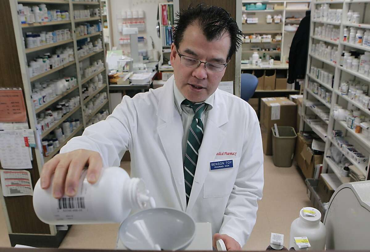 Pharmacist Benson Toy shakes ibuprofen into a pill counter at the Marin Medical Pharmacy in San Rafael.