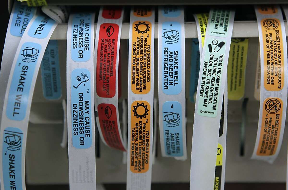 Advisory labels for prescription medications are arranged at the pharmacy.