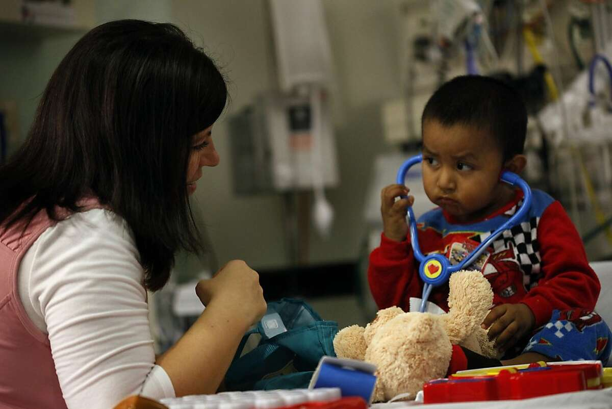 Kristen Beckler, a child life specialist works with Ivan Gonzalez, 2, in the pediatric emergency department, Monday December 23, 2013, at the Packard Children's Hospital, in Palo Alto, Calif.