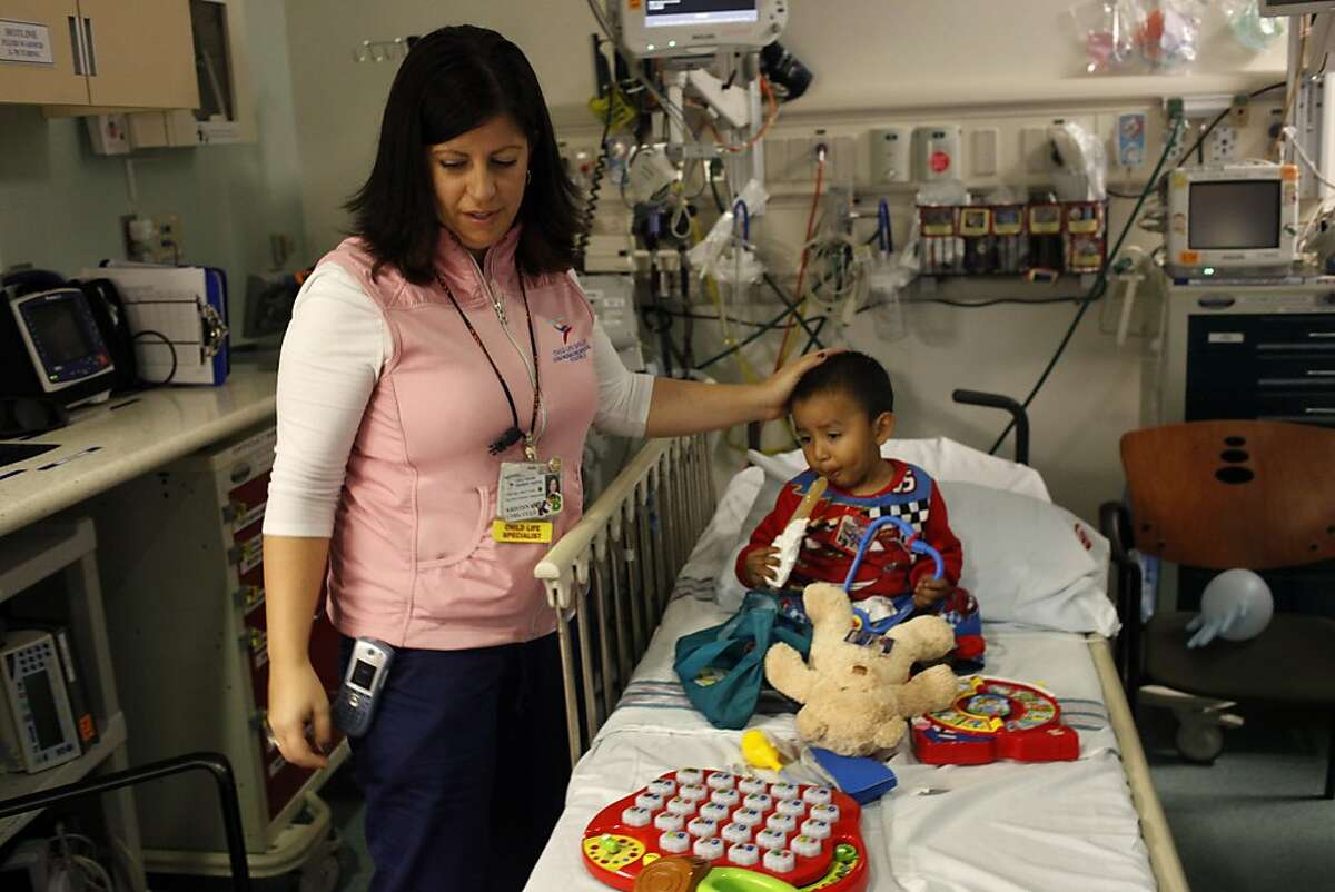 Child life specialist, Kristen Beckler, pats Ivan Gonzalez, 2, in the head after working with him in the pediatric emergency department, Monday December 23, 2013, at the Packard Children's Hospital, in Palo Alto, Calif.