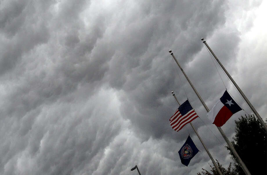 Flags fly at half-staff at the San Antonio Fire Academy on Dec. 21, in honor of Police Officer Robert Deckard, who died a day earlier from a gunshot wound to the head. Photo: Lisa Krantz / San Antonio Express-News / SAN ANTONIO EXPRESS-NEWS