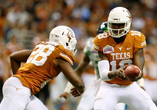 Quarterback Tyrone Swoopes #18 hands the ball off to running back Malcolm Brown. Photo: Ronald Martinez, Getty Images