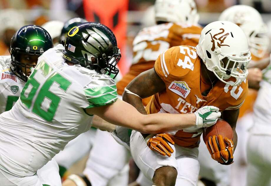 Running back Joe Bergeron #24 of the Longhorns carries the ball as defensive tackle Taylor Hart #66 of the Ducks defends. Photo: Ronald Martinez, Getty Images