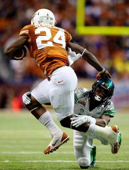 Running back Joe Bergeron #24 of the Longhorns tries to avoid a tackle by cornerback Ifo Ekpre-Olomu #14 of the Ducks. Photo: Ronald Martinez, Getty Images