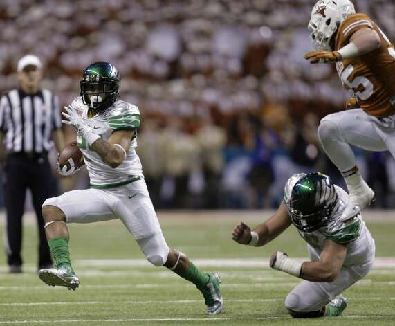 Oregon's Thomas Tyner, left, rushes as Texas' Dalton Santos pursues. Photo: Eric Gay, Associated Press