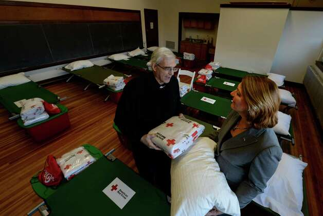 Rev. Dominic Ingemie, left, speaks with Mayor Elect Joanne Yepsen at St. Peter's Parish Center Monday afternoon, Dec. 30, 2013, in Saratoga Springs, N.Y. The church is setup as a shelter for the homeless to escape from the extreme cold weather which was forecast for this week. Code Blue, an expanding system that helps the homeless find warm beds on frigid nights, will be severely tested this week, when it stays in effect for a record six straight nights in Albany and Saratoga Springs. (Skip Dickstein / Times Union) Photo: SKIP DICKSTEIN / 0025201A