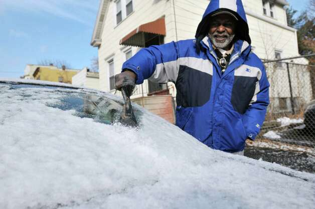 Larry Burden scrapes the ice off his car Monday morning, Dec. 30, 2013, outside his home on Elk St. in Albany, N.Y. (Paul Buckowski / Times Union) Photo: PAUL BUCKOWSKI / 00025197A