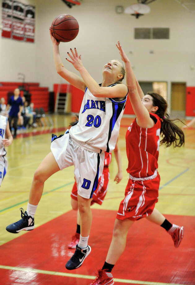Darien's Kelly Karczewski lays the ball in while under pressure from Greenwich's Jamie Kockenmeister during the championship final of the 19th annual Tony LaVista Basketball Tournament at New Canaan High School in New Canaan, Conn., on Monday, Dec. 30, 2013. Greenwich won 66-36. Photo: Jason Rearick / Stamford Advocate