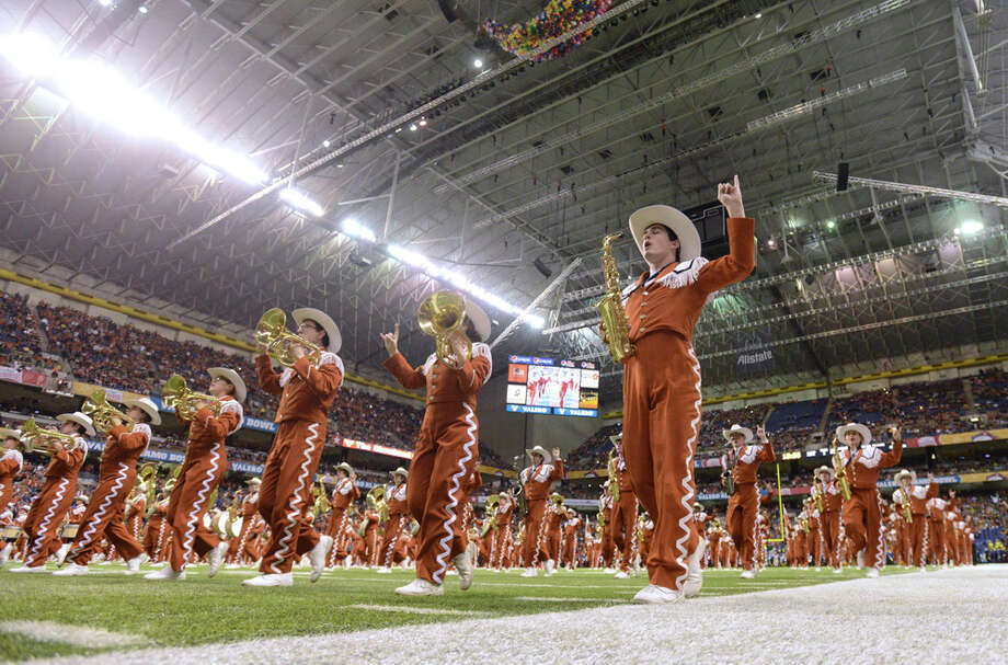 The Texas Longhorns marching band takes the field before the Valero Alamo Bowl in the Alamodome on Monday, Dec. 30, 2013. Photo: Billy Calzada, San Antonio Express-News / San Antonio Express-News