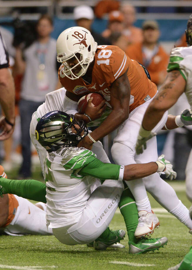 Texas quarterback Tyrone Swoopes runs over Oregon defensive back Tyree Robinson during second-half action of the Valero Alamo Bowl in the Alamodome on Monday, Dec. 30, 2013. Photo: Billy Calzada, San Antonio Express-News / San Antonio Express-News