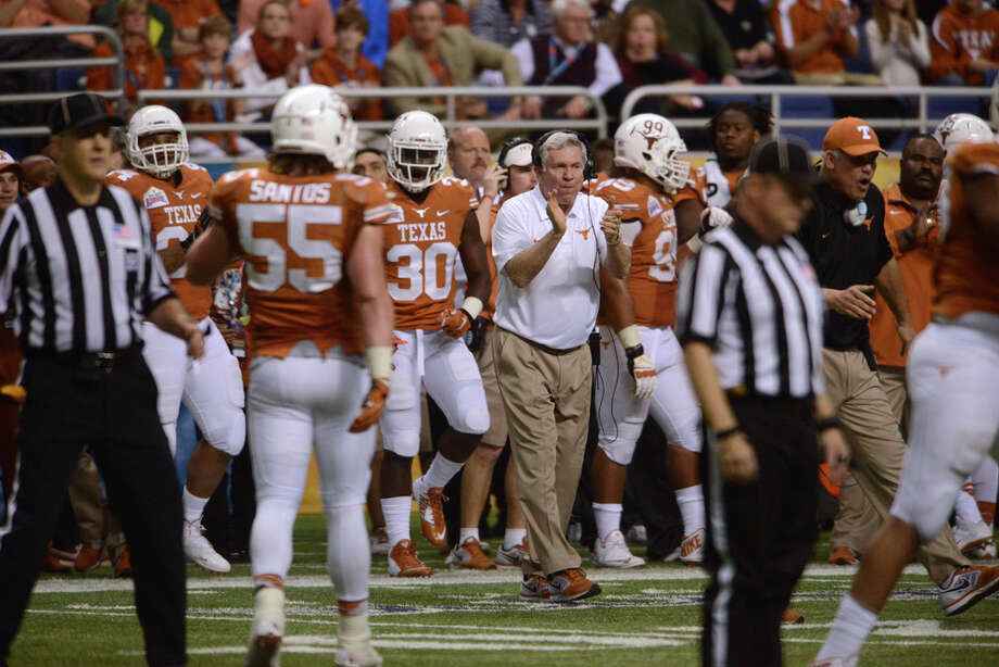 Coach Mack Brown of Texas encourages his team as they go down in defeat to Oregon in the Valero Alamo Bowl in the Alamodome on Monday, Dec. 30, 2013. The game was Brown's last as beach coach of the Texas team. Photo: Billy Calzada, San Antonio Express-News / San Antonio Express-News
