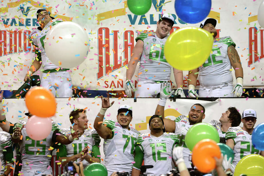 The Oregon Ducks celebrate as balloons and confetti are poured on them after they defeated Texas, 30-7, in the Valero Alamo Bowl in the Alamodome on Monday, Dec. 30, 2013. Quarterback Marcus Mariota is at top left; senior tackle Taylor Hart (66) and senior defensive tackle Wade Kelikipi (92) join him on the top row. Photo: Billy Calzada, San Antonio Express-News / San Antonio Express-News