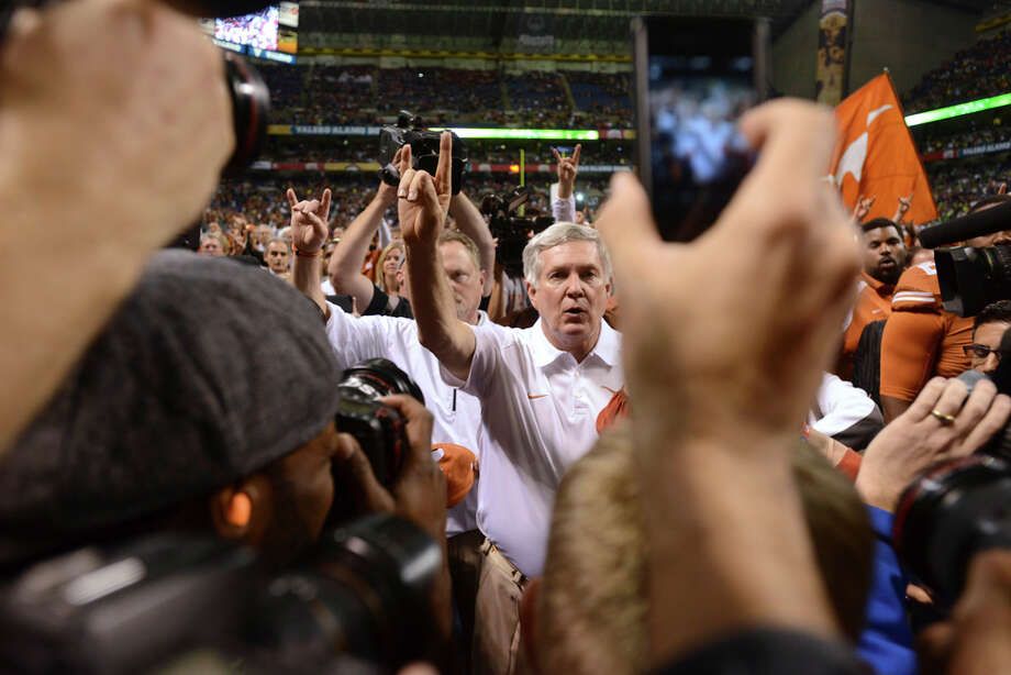 "Texas head coach Mack Brown sings the Eyes of Texas and shows the ""Hook 'em Horns"" sign after his last game as coach of the team. Brown's Longhorns lost to Oregon, 30-7, in the Valero Alamo Bowl in the Alamodome on Monday, Dec. 30, 2013. Photo: Billy Calzada, San Antonio Express-News / San Antonio Express-News"