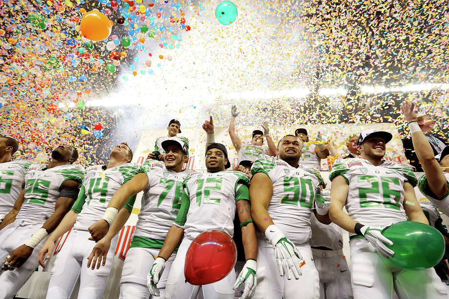 Members of the Oregon Ducks celebrate after the Valero Alamo Bowl with the Texas Longhorns Monday Dec. 30, 2013 at the Alamodome. Oregon won 30-7. Photo: Edward A. Ornelas, San Antonio Express-News / © 2013 San Antonio Express-News