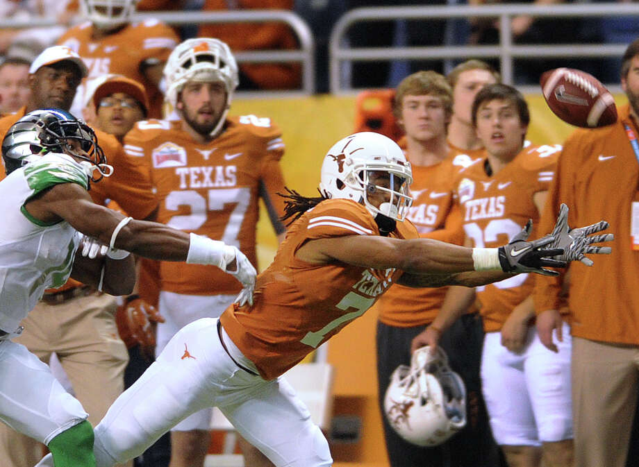 Texas receiver Marcus Johnson dives for a ball just out of his reach as Oregon cornerback Ifo Ekpe-Olomu gives chase during first-half action of the Valero Alamo Bowl in the Alamdome on Monday, Dec. 30, 2013. Photo: Billy Calzada, San Antonio Express-News / San Antonio Express-News