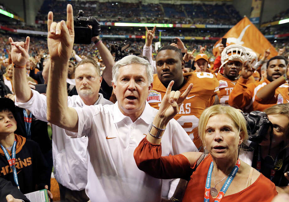 Texas Longhorns head coach Mack Brown and his wife Sally flash the hook 'em horns during the Eyes of Texas after the Valero Alamo Bowl with the Oregon Ducks Monday Dec. 30, 2013 at the Alamodome. Oregon won 30-7. Photo: Edward A. Ornelas, San Antonio Express-News / © 2013 San Antonio Express-News
