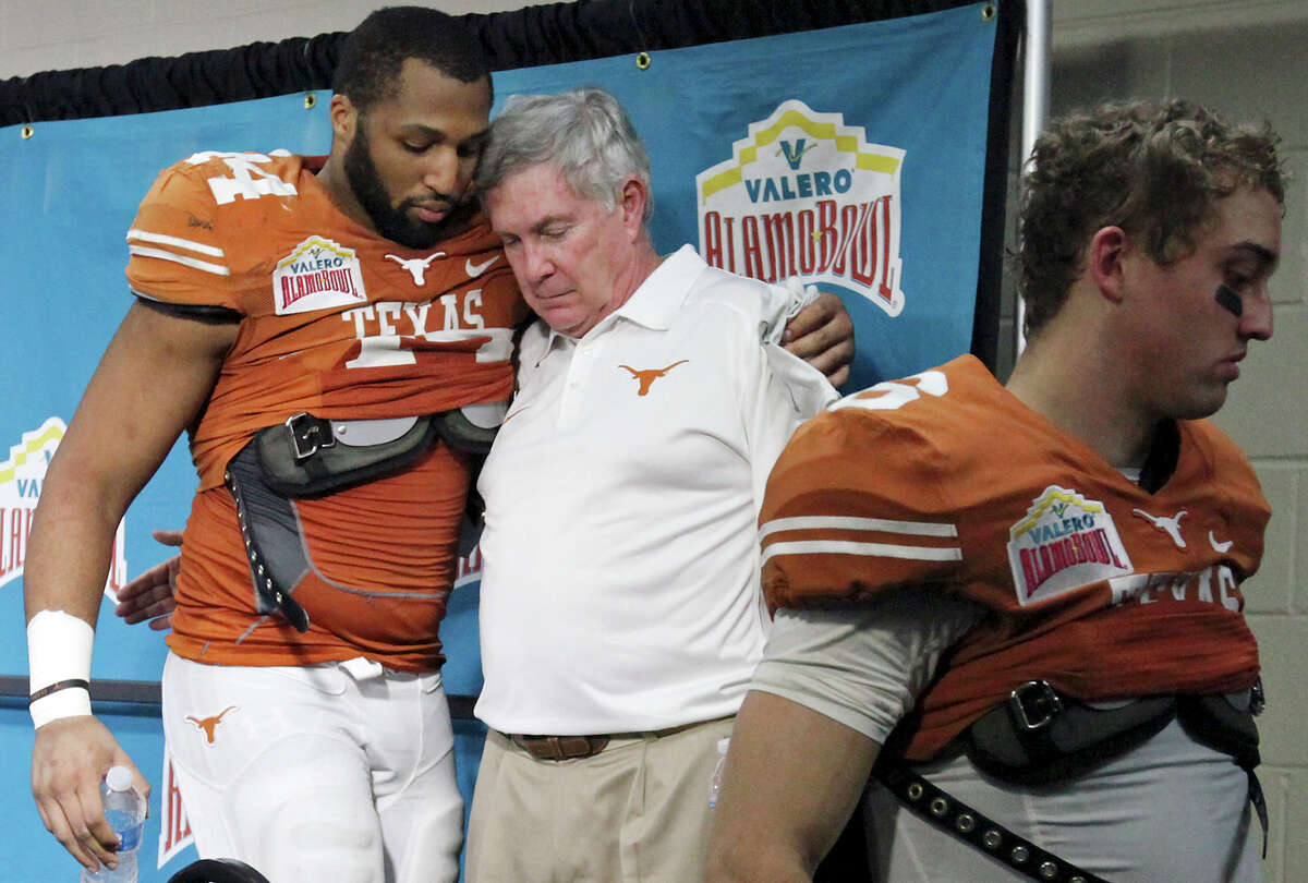 Texas Longhorns' Jackson Jeffcoat (from left) hugs head coach Mack Brown as Case McCoy walks off after a press conference for the Valero Alamo Bowl with the Oregon Ducks Monday Dec. 30, 2013 at the Alamodome. Oregon won 30-7.