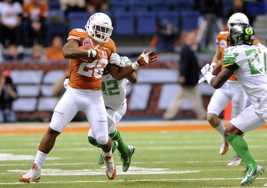 Texas running back Malcolm Brown is tackled by Cody Carriger of the Oregon Ducks during first-half action of the Valero Alamo Bowl in the Alamodome on Monday, Dec. 30, 2013. Photo: Billy Calzada, San Antonio Express-News / San Antonio Express-News
