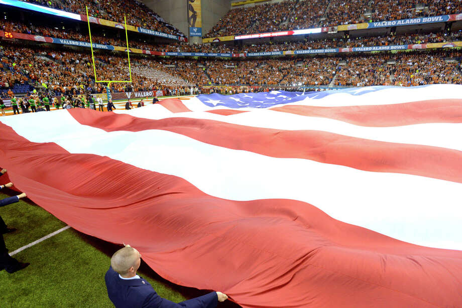 A football field-sized Old Glory is displayed during the playing of the Star Spangled Banner before the Valero Alamo Bowl in the Alamdome on Monday, Dec. 30, 2013. Photo: Billy Calzada, San Antonio Express-News / San Antonio Express-News