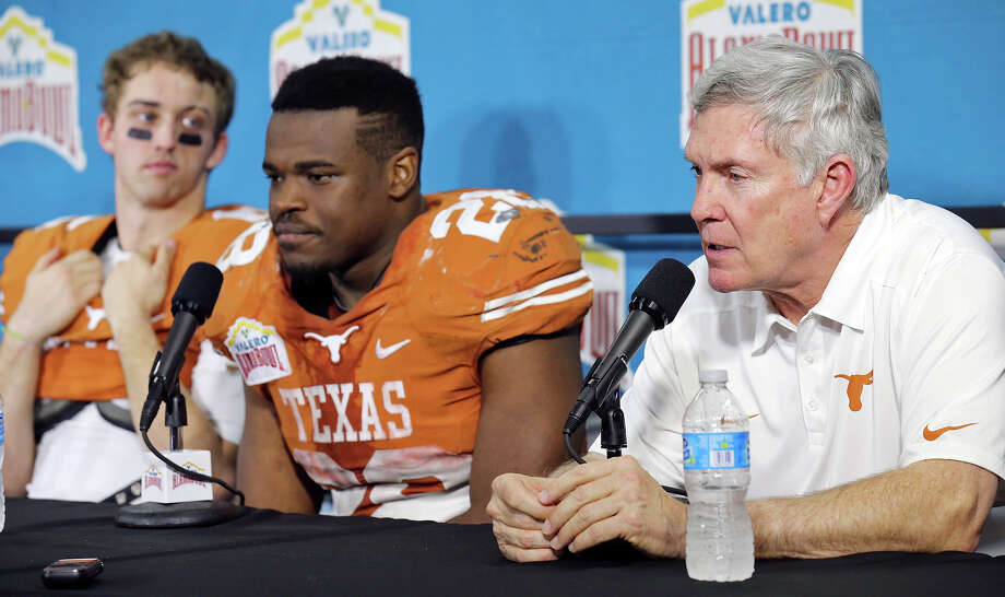 Texas Longhorns' Case McCoy, (from left) and Malcolm Brown listen to head coach Mack Brown speak during a press conference after the Valero Alamo Bowl with the Oregon Ducks Monday Dec. 30, 2013 at the Alamodome. Oregon won 30-7. Photo: Edward A. Ornelas, San Antonio Express-News / © 2013 San Antonio Express-News