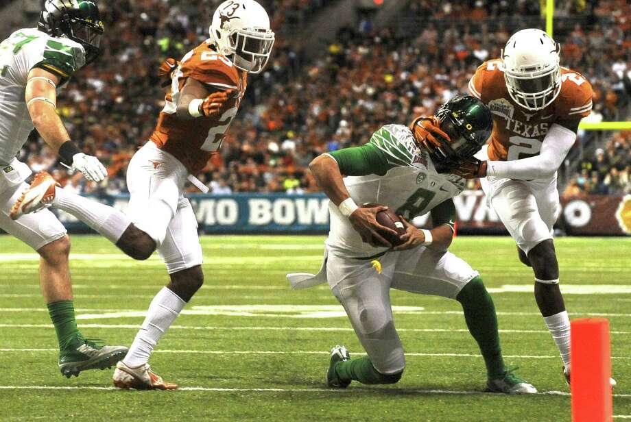 Oregon quarterback Marcus Mariota (8) is grabbed by the helmet by Mykkele Thompson of Texas during first-half action of the Valero Alamo Bowl in the Alamdome on Monday, Dec. 30, 2013. Photo: Billy Calzada, San Antonio Express-News / San Antonio Express-News