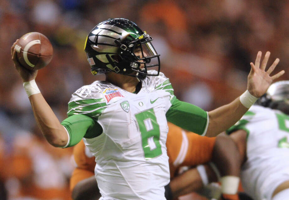 Oregon quarterback Marcus Mariota passes against Texas during first-half action of the Valero Alamo Bowl in the Alamdome on Monday, Dec. 30, 2013. Photo: Billy Calzada, San Antonio Express-News / San Antonio Express-News