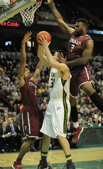 Siena's Brett Bisping is double guarded by Fordham's Mandell Thomas, left, and Tavion Leonard during