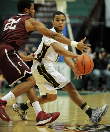 Siena's Marquis Wright passes the ball around Fordham's Jermaine Myers during a basketball game at t