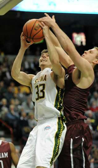 Siena's Rob Poole is guarded by Fordham's Ryan Canty as he drives to the basket during a basketball