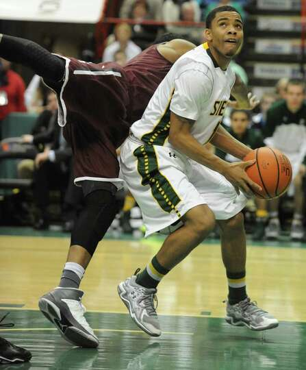 Siena's Marquis Wright fakes out Fordham's Branden Frazier under the net and gets fouled during a ba