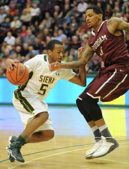 Siena's Evan Hymes dribbles around Fordham's Branden Frazier during a basketball game at the Times U