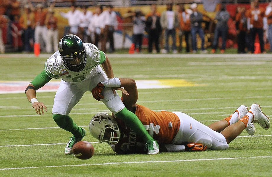 Oregon quarterback Marcus Mariota fumbles as he is hit by Texas defensive end Jackson Jeffcoat during first-half action of the Valero Alamo Bowl in the Alamdome on Monday, Dec. 30, 2013. The ball rolled out of bounds and Oregon retained possession. Photo: Billy Calzada, San Antonio Express-News / San Antonio Express-News