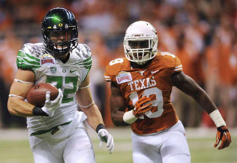 Oregon tight end Evan Baylis (32) runs for yardage after a reception as Texas linebacker Peter Jinkens chases him down during first-half action of the Valero Alamo Bowl in the Alamodome on Monday, Dec. 30, 2013. Photo: Billy Calzada, San Antonio Express-News / San Antonio Express-News