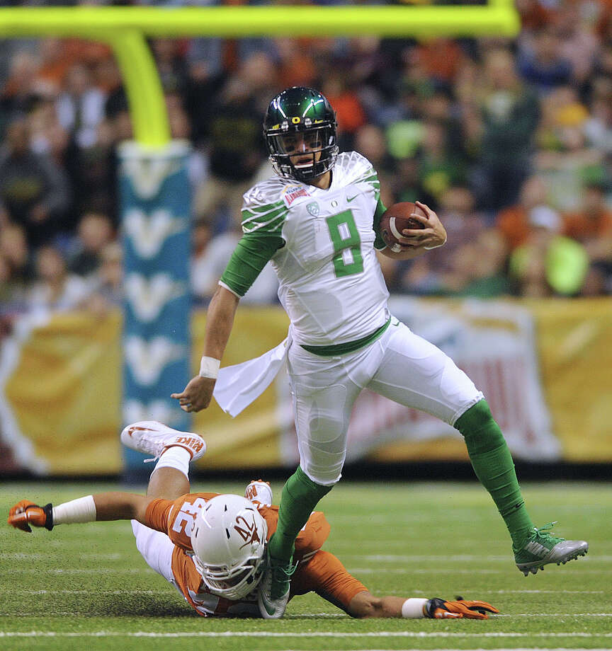 Oregon quarterback Marcus Mariota gets away fro Caleb Bluiett of Texas during first-half action of the Valero Alamo Bowl in the Alamodome on Monday, Dec. 30, 2013. Photo: Billy Calzada, San Antonio Express-News / San Antonio Express-News