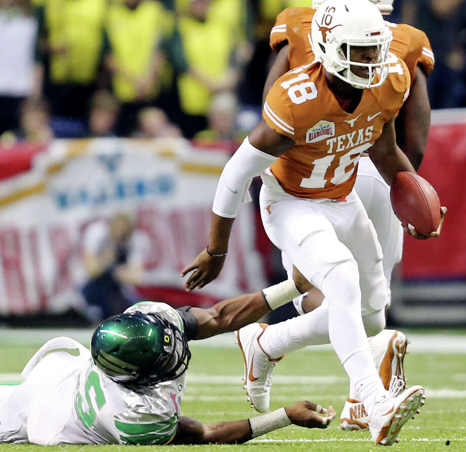 Texas Longhorns' Tyrone Swoopes looks for room around Oregon Ducks' Boseko Lokombo during second half action of the Valero Alamo Bowl Monday Dec. 30, 2013 at the Alamodome. Photo: Edward A. Ornelas, San Antonio Express-News / © 2013 San Antonio Express-News
