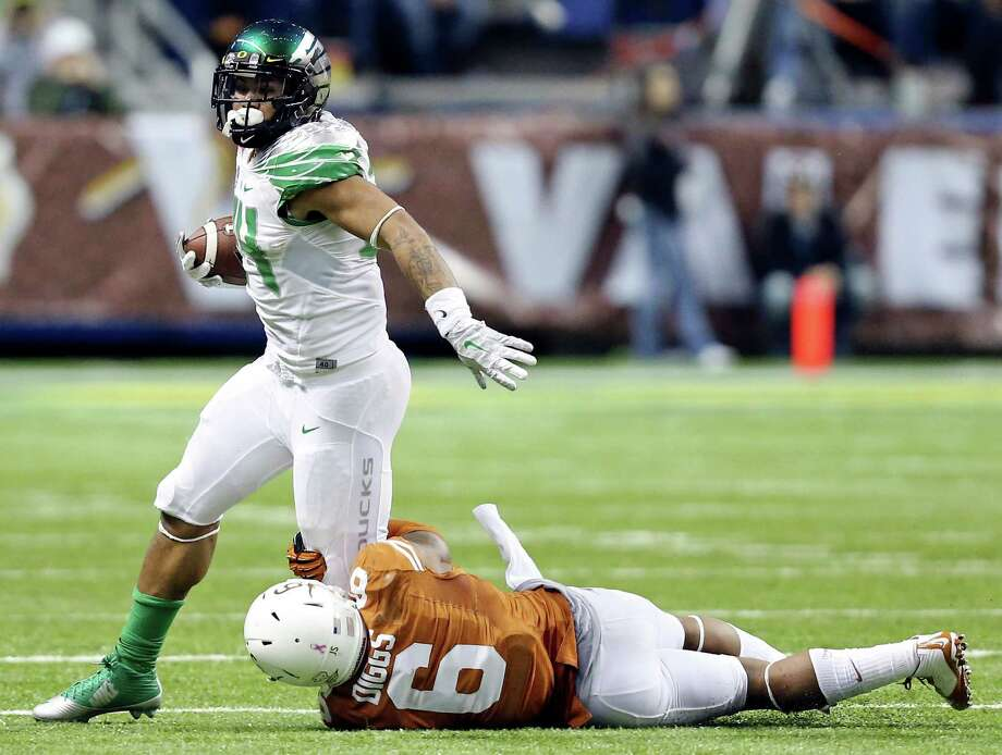 Oregon Ducks' Thomas Tyner tries to shake the tackle of Texas Longhorns' Quandre Diggs during second half action of the Valero Alamo Bowl Monday Dec. 30, 2013 at the Alamodome. Photo: Edward A. Ornelas, San Antonio Express-News / © 2013 San Antonio Express-News