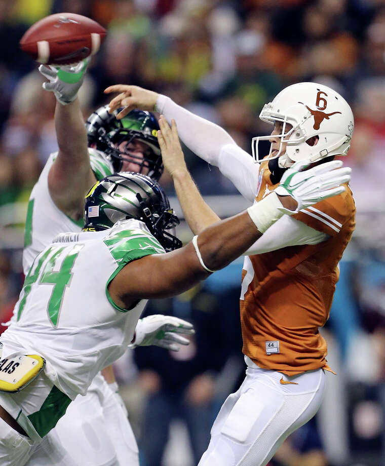 Texas Longhorns' Case McCoy passes under pressure from Oregon Ducks' DeForest Buckner and Oregon Ducks' Taylor Hart (rear) during first half action of the Valero Alamo Bowl Monday Dec. 30, 2013 at the Alamodome. Photo: Edward A. Ornelas, San Antonio Express-News / © 2013 San Antonio Express-News
