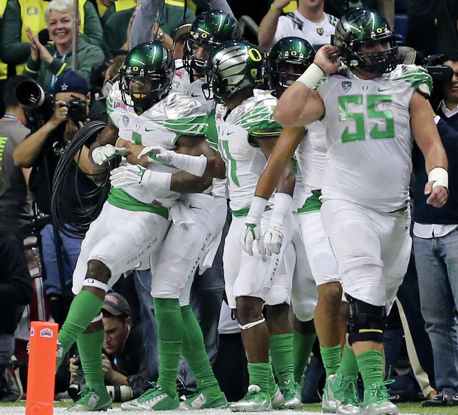 Oregon Ducks' Josh Huff (left) is congratulated by teammates after scoring a touchdown during first half action of the Valero Alamo Bowl against the Texas Longhorns Monday Dec. 30, 2013 at the Alamodome. Photo: Edward A. Ornelas, San Antonio Express-News / © 2013 San Antonio Express-News