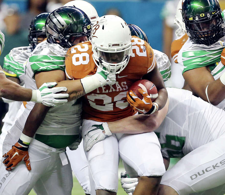Texas Longhorns'  Malcolm Brown is tackled by Oregon Ducks defenders during first half action of the Valero Alamo Bowl Monday Dec. 30, 2013 at the Alamodome. Photo: Edward A. Ornelas, San Antonio Express-News / © 2013 San Antonio Express-News