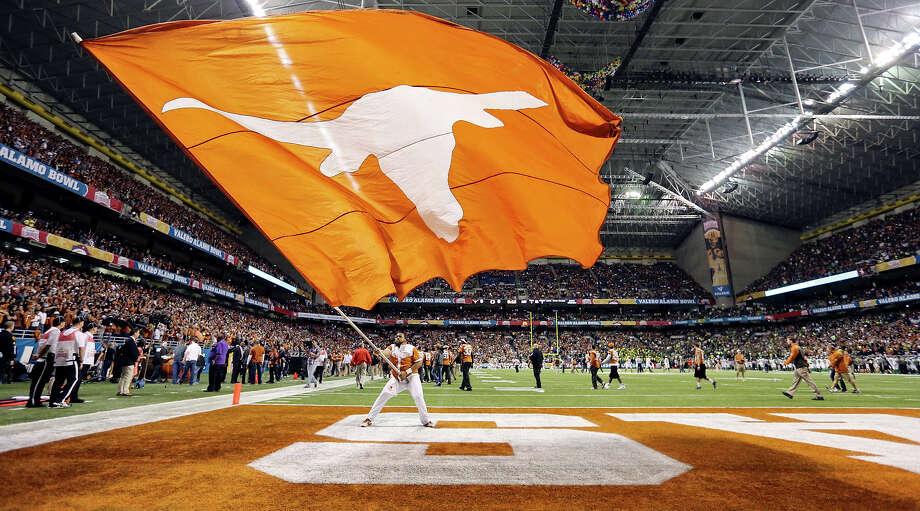A Texas Longhorns cheerleader waves a Texas flag before the Valero Alamo Bowl with the Oregon Ducks Monday Dec. 30, 2013 at the Alamodome. Photo: Edward A. Ornelas, San Antonio Express-News / © 2013 San Antonio Express-News