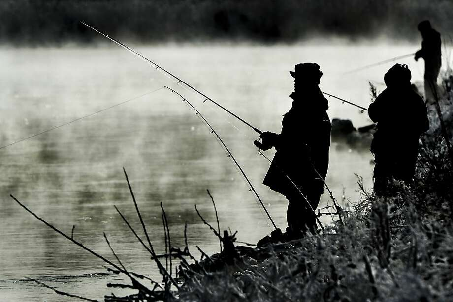 Fishermen cast their lines as steam rises from Powerton Lake, near Pekin Ill., on a frigid Monday, Dec. 30, 2013. Water warmed from nearby power plants is a favorite for fishermen during the winter months. (AP Photo/Peoria Journal Star/Ron Johnson) Photo: Ron Johnson, Associated Press