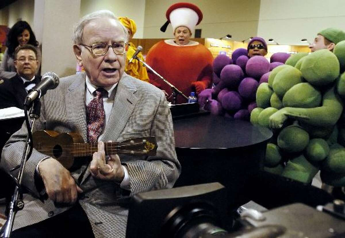 Fruit of the Loom Warren Buffett plays the ukelele at the Fruit of the Loom stand at the Qwest Center in Omaha, Neb., while touring exhibits prior to the annual Berkshire Hathaway shareholders meeting in April 2005.