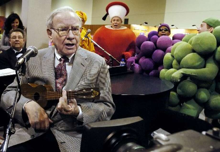 Fruit of the Loom  Warren Buffett plays the ukelele at the Fruit of the Loom stand at the Qwest Center in Omaha, Neb., while touring exhibits prior to the annual Berkshire Hathaway shareholders meeting in April 2005. Photo: Nati Harnik, AP