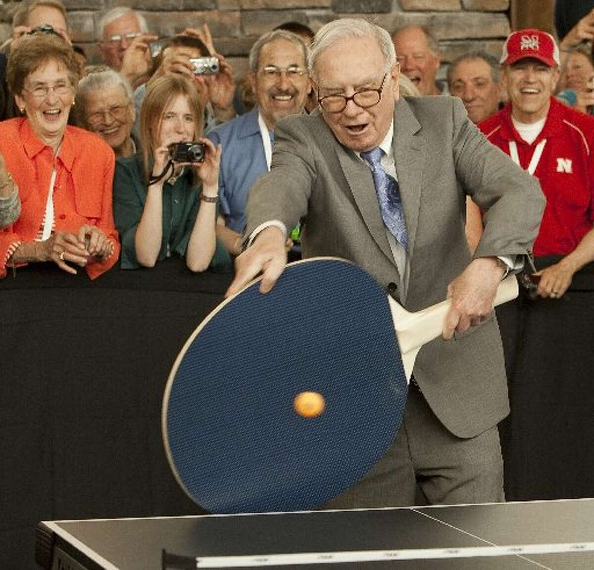 Borsheims Fine Jewelry Warren Buffett uses a super large paddle to play table tennis against junior champion Ariel Hsing, outside a Berkshire Hathaway-owned Borsheim's jewelry store in Omaha, Neb. in 2012.