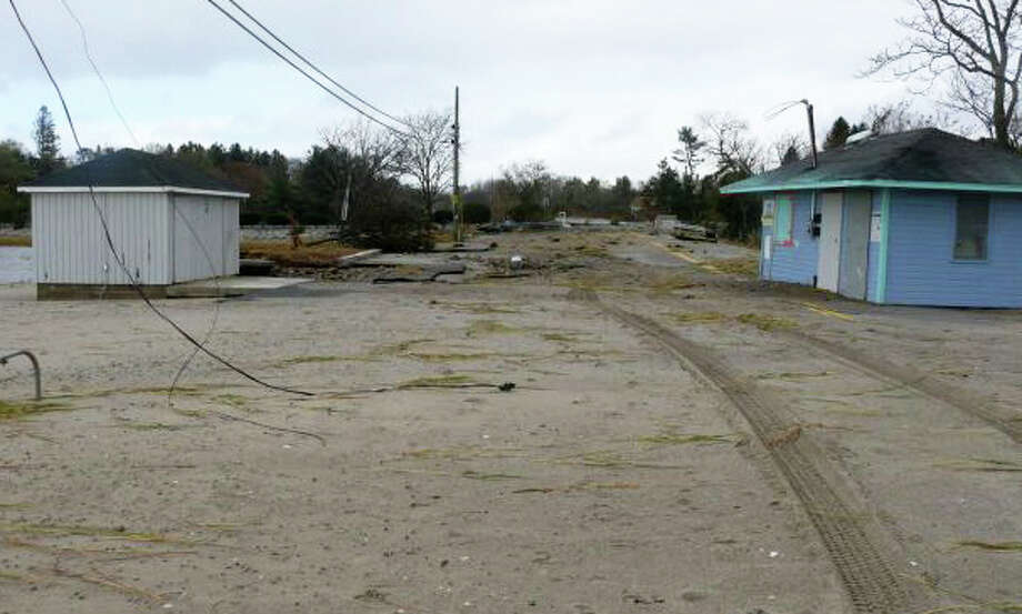 The Southport Beach snack bar, at right, was pushed across Pequot Avenue from the beach by Superstorm Sandy in October 2012, while the road itself was inundated with sand. Town officials now want a mobile vendor to provide concession services at the beach. Photo: File Photo / Fairfield Citizen