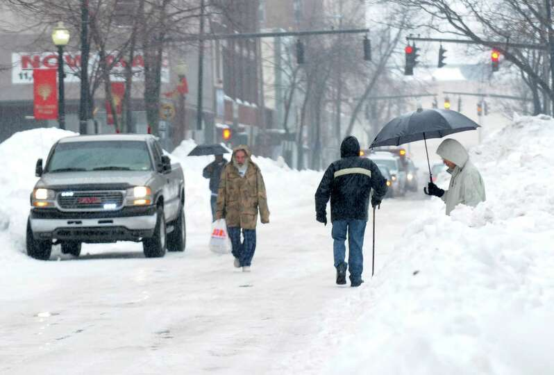 Pedestrians continue to struggle to get around the city as they walk around vehicles and snowbanks o