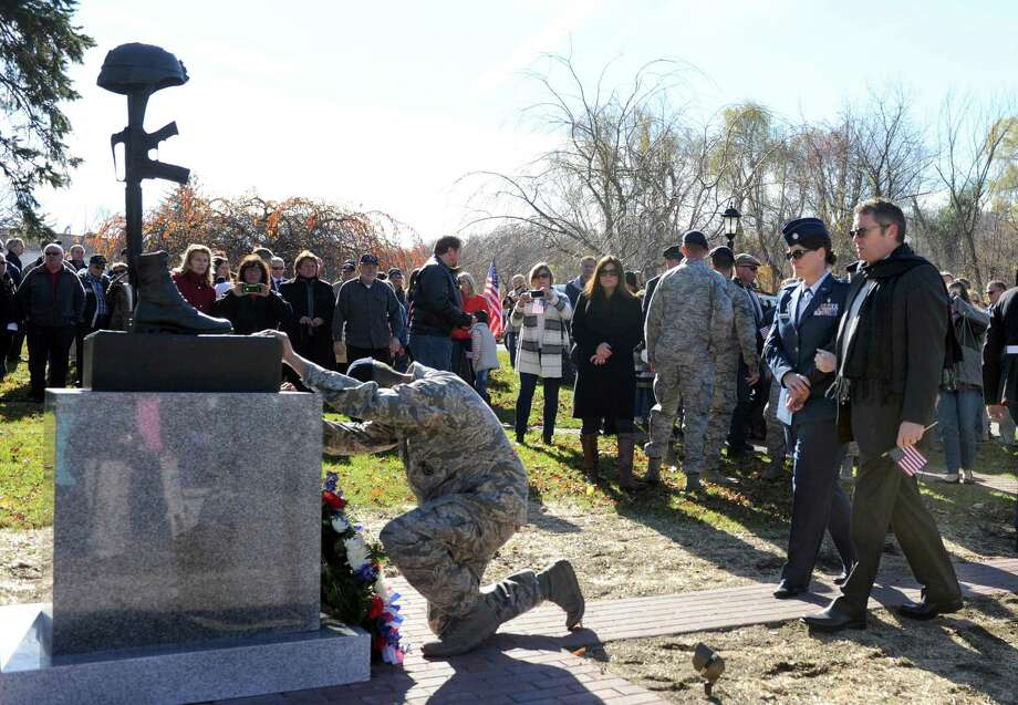 "Maj. Linda Rohatsch and Dr. Robert Rohatsch, Todd Lobraico's mother and step-father, approach a monument dedicated in part to their son. The town of New Fairfield, Conn. recognized Veterans Day with a ceremony at Veterans Green that included the dedication of a monument honoring Staff Sgt. Todd "" T.J."" Lobraico and other town residents killed in action, Monday. Nov. 11, 2013.  Lobraico, serving in Afghanistan, died Sept. 5. Photo: Carol Kaliff / The News-Times"