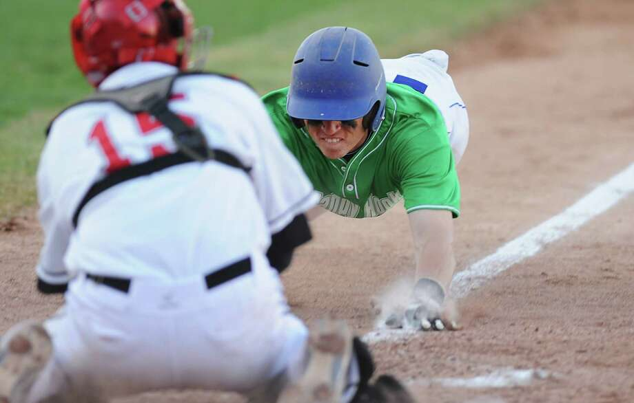 "Newtown's Steven Conway slides into home as Pomperaug catcher Steve Harrison tags him out during Newtown's 5-4 win over Pomperaug in the baseball ""Game to Remember"" at The Ballpark at Harbor Yard in Bridgeport, Conn. on Thursday, April 25, 2013.  The game was played to honor and acknowledge Sandy Hook Elementary School and the first responders of the December 14 tragedy.  All proceeds benefitted the Sandy Hook Volunteer Fire Department. Photo: Tyler Sizemore / The News-Times"